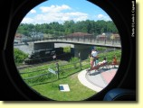Porthole: A family looks on as helper locomotives pass under Jackson Street.  Framing this photo is the porthole window of our restored PRR N5C caboose.